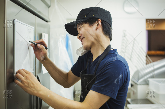 Man working in a bakery, wearing baseball cap and apron, writing note on small whiteboard, using phone and smiling
