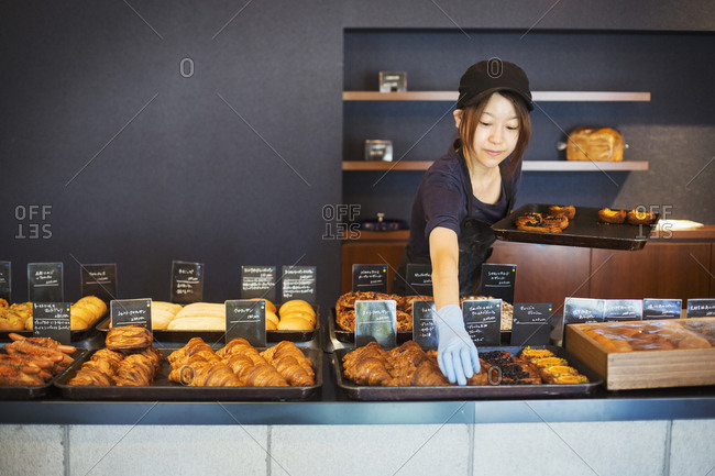Woman working in a bakery, placing freshly baked croissants and cakes on large trays on a counter