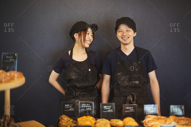 Smiling man and woman wearing baseball cap and apron standing in a bakery, trays with freshly baked goods