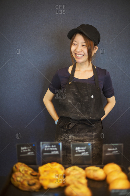 Smiling woman wearing baseball cap and apron standing in a bakery, trays with freshly baked goods