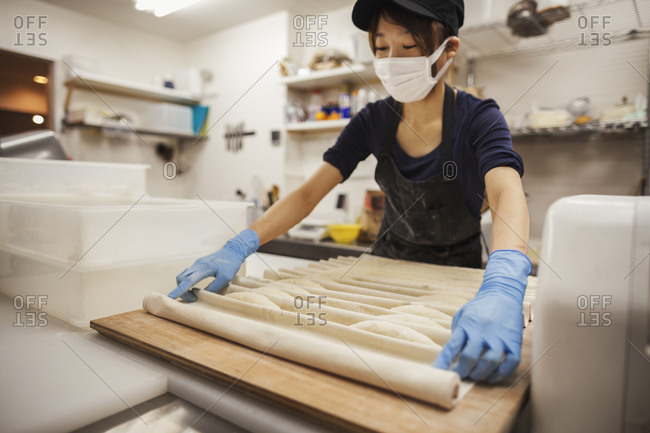 Woman working in a bakery, wearing protective gloves and mask, placing dough on large wooden board