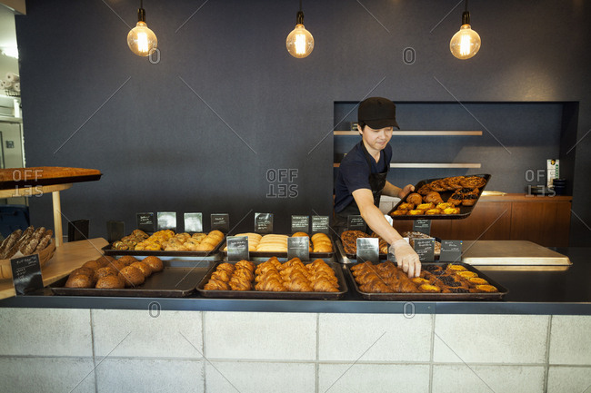 Man working in a bakery, placing freshly baked croissants and cakes on large trays on a counter