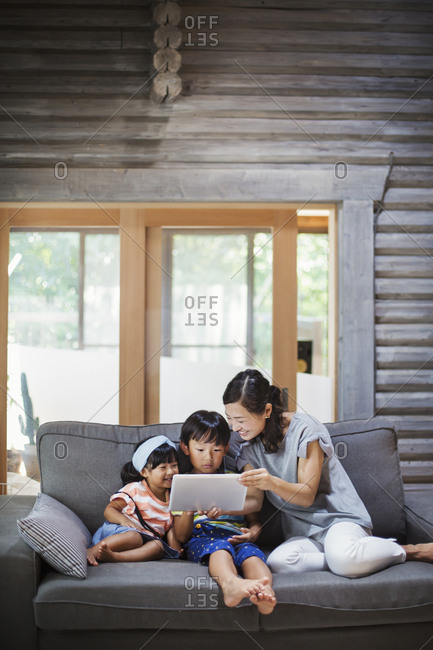 Woman, boy and young girl sitting on a grey sofa, looking at digital tablet