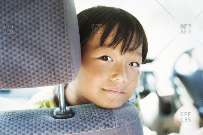 Boy with black hair sitting in a car, looking at camera