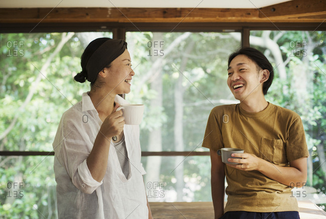 Man and woman standing indoors, holding coffee mugs, looking at each other, smiling