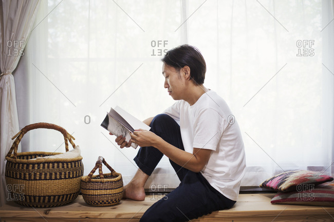 Man sitting indoors on a wooden bench with baskets, crossed legs, reading