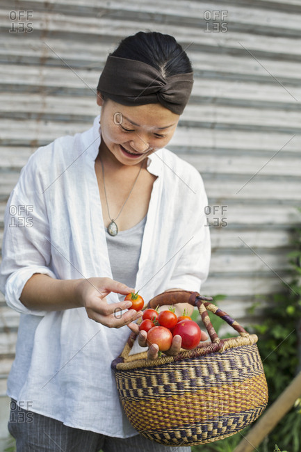 Smiling woman standing outdoors, holding basket and freshly picked tomatoes