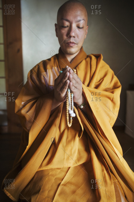 Buddhist monk with shaved head wearing golden robe kneeling indoors in a temple, holding mala, praying