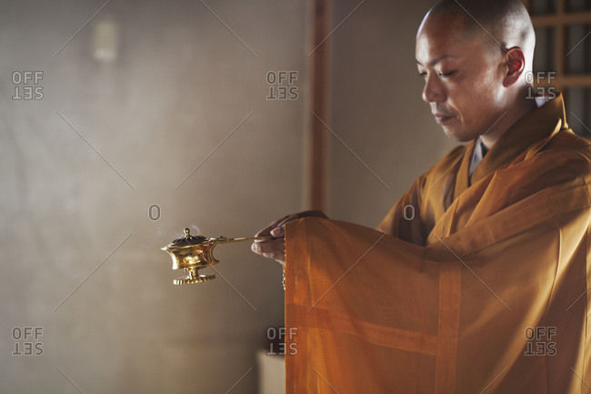 Side view of Buddhist monk with shaved head wearing golden robe kneeling indoors in a temple, holding incense burner