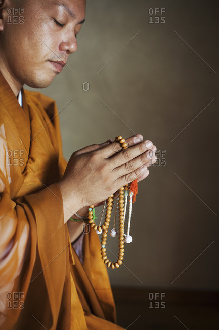Side view of Buddhist monk with shaved head wearing golden robe kneeling indoors in a temple, holding mala, praying