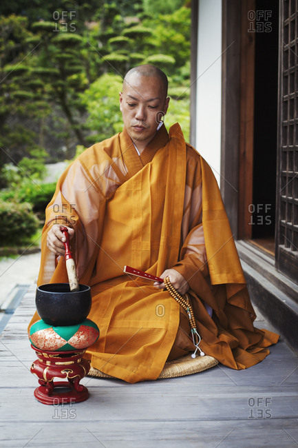 Buddhist monk with shaved head wearing golden robe sitting on floor outdoors, using singing bowl