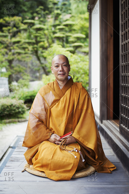 Buddhist monk with shaved head wearing golden robe sitting on floor outdoors, holding mala, smiling at camera