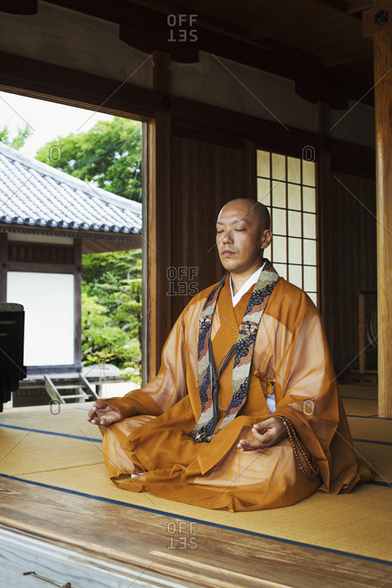 Buddhist monk with shaved head wearing golden robe sitting cross legged on the floor, meditating, Buddhist hand gesture