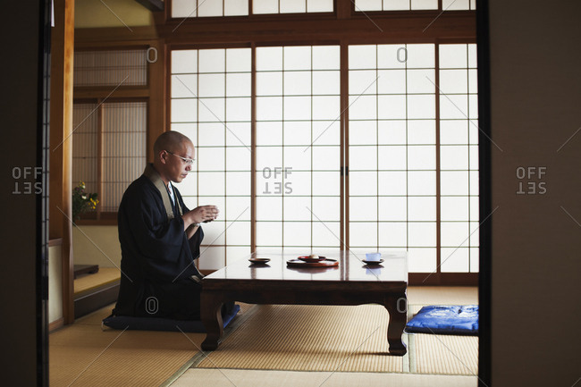 Side view of Buddhist monk with shaved head wearing black robe kneeling indoors at a table, holding bowl of tea