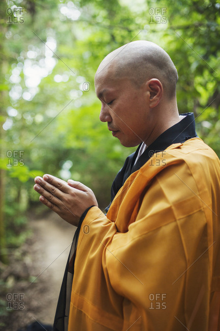 Side view of Buddhist monk with shaved head wearing black and yellow robe, standing outdoors, meditating
