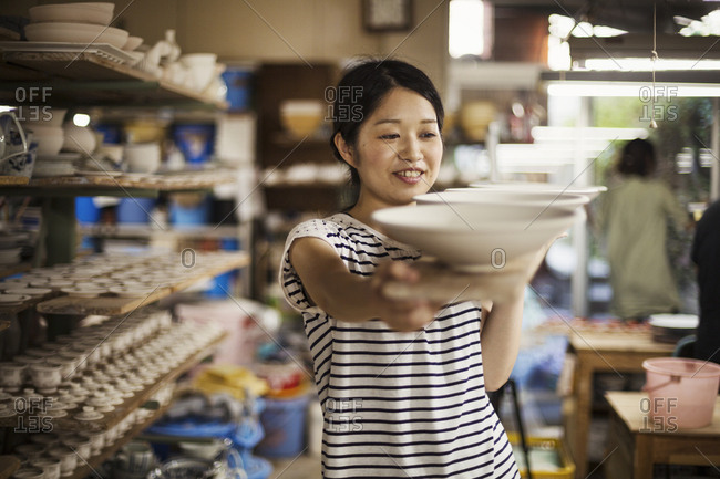 Woman standing in a workshop, carrying long wooden tray with porcelain bowls