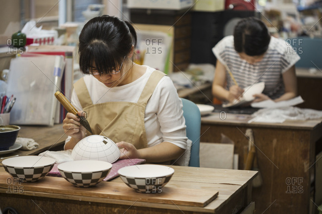 Woman working in a Japanese porcelain workshop, painting geometric pattern onto white bowls with paintbrush