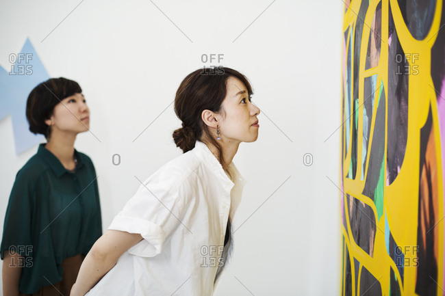 Two women standing in an art gallery, looking at an abstract modern painting