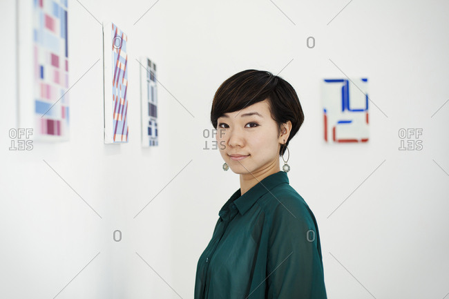 Woman with short black hair wearing green shirt standing in art gallery, looking at camera