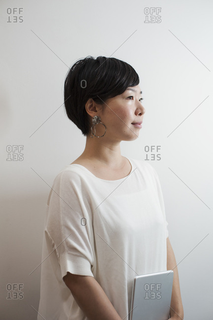 Profile view of woman with sort black hair wearing white shirt standing in art gallery