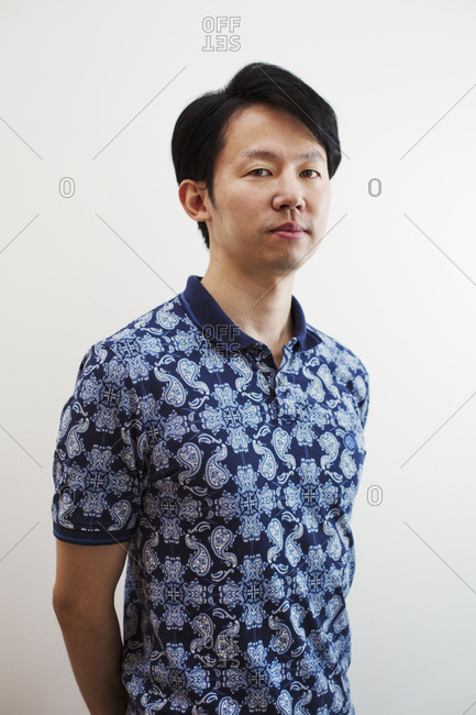 Portrait of man with short black hair wearing blue patterned shirt standing in art gallery, looking at camera