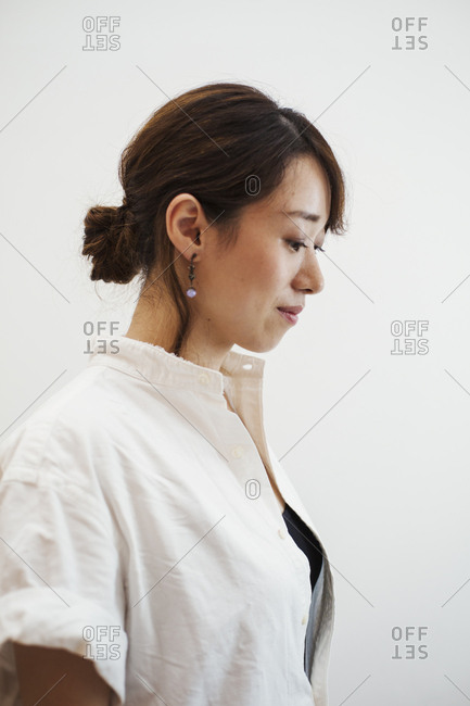 Profile view of woman with ponytail wearing white shirt standing in art gallery