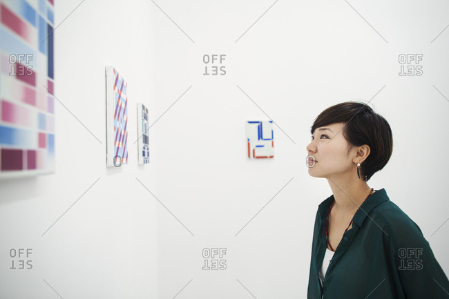 Woman with short black hair wearing green shirt standing in art gallery, looking at modern painting