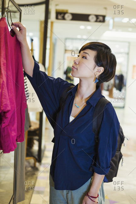 Woman with black hair wearing blue shirt standing indoors, looking at clothing in a shop