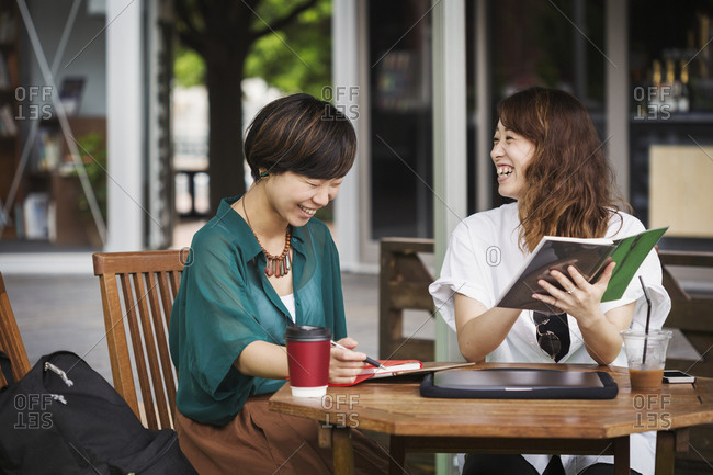 Two women with black hair wearing green and white shirt sitting at table in a street cafe, holding digital tablet, smiling