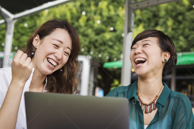 Two women with black hair wearing green and white shirt sitting in front of laptop at table in a street cafe, laughing