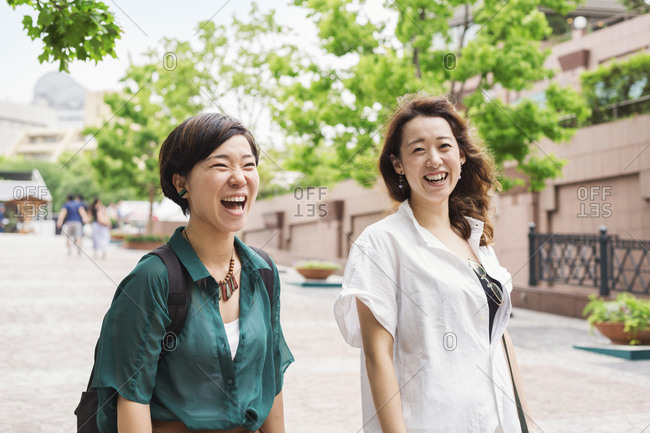 Two women with black hair wearing white and green shirt walking along street, smiling