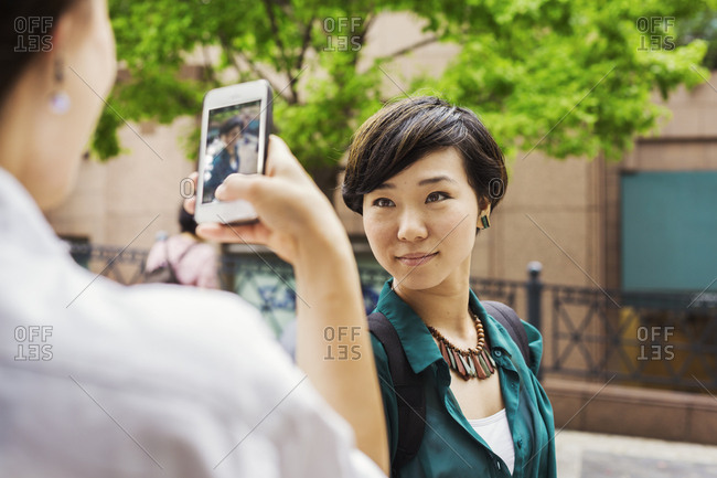 Two women with black hair wearing white and green shirt standing outdoors, taking picture with mobile phone, smiling