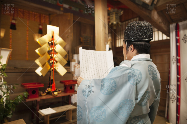 Rear view of priest holding scroll at Shinto Sakurai Shrine, Fukuoka, Japan