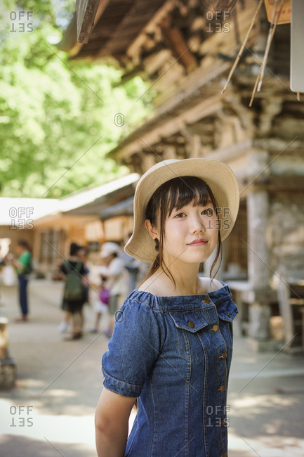 Young woman wearing blue dress and hat at Shinto Sakurai Shrine, Fukuoka, Japan