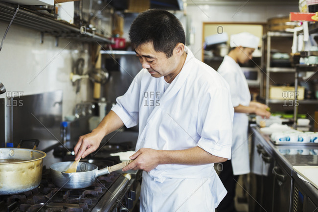 Chef working in the kitchen of a Japanese sushi restaurant, cooking on stove