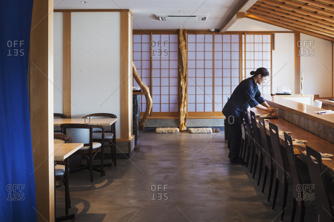 Waitress standing at a counter in a Japanese sushi restaurant, preparing place settings