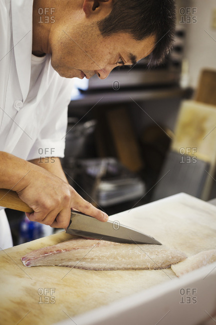 Chef working at a counter at a Japanese sushi restaurant, slicing fillet of fish
