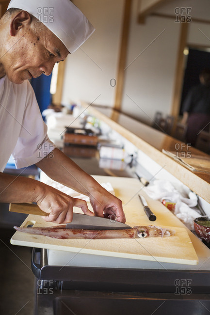 Chef working at a counter at a Japanese sushi restaurant, cutting a squid