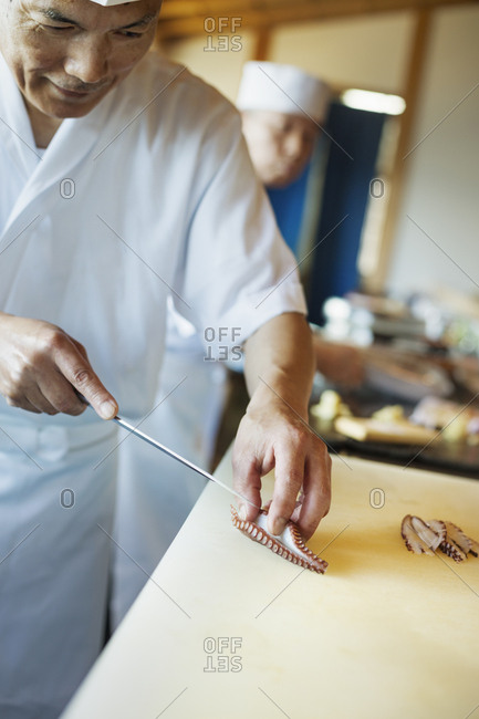 Two chefs working at a counter at a Japanese sushi restaurant, slicing octopus tentacle