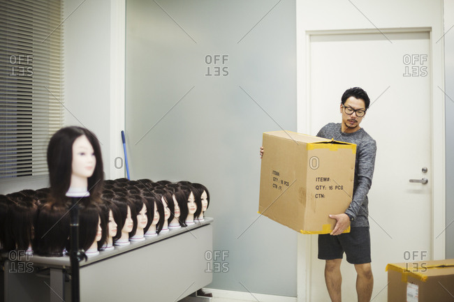 Bearded man wearing glasses standing indoors, carrying cardboard box, large group of mannequin heads with brown wigs on table