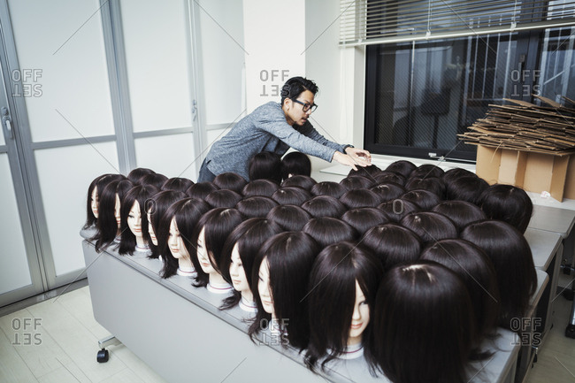 Bearded man wearing glasses standing indoors, arranging mannequin heads with brown wigs