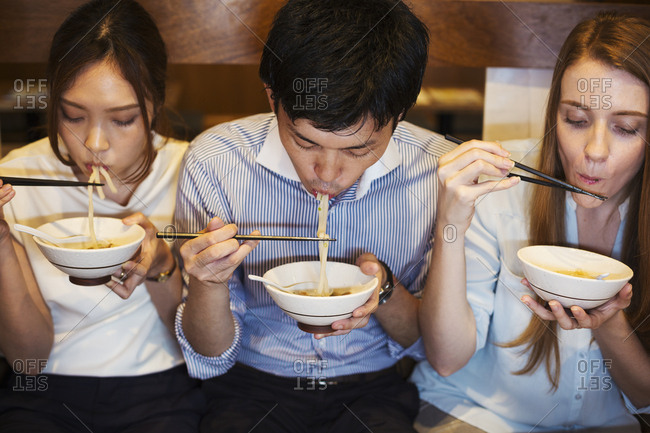 High angle view of three people sitting side by side at a table in a restaurant, eating from bowls using chopsticks