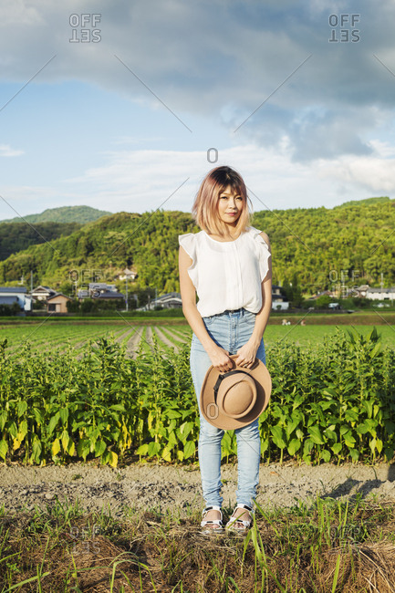 A young woman holding a sun hat, standing on a road by open fields of rice paddies