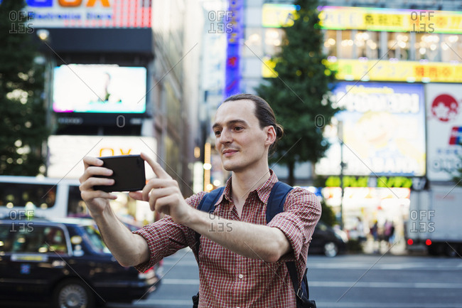 A young man, a Caucasian visitor to Tokyo, on the street using his smart phone and taking photographs
