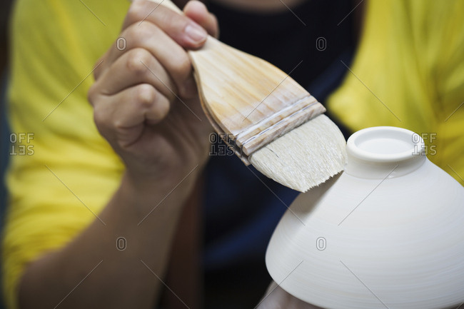 Close up of person working in a Japanese porcelain workshop, glazing white bowls with paintbrush
