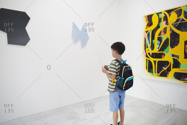 Boy with short black hair wearing backpack standing in art gallery, holding pen and paper, looking at modern painting