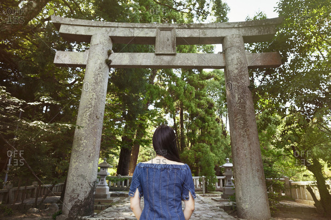 Rear view of young woman wearing blue dress standing at Shinto Sakurai Shrine, Fukuoka, Japan