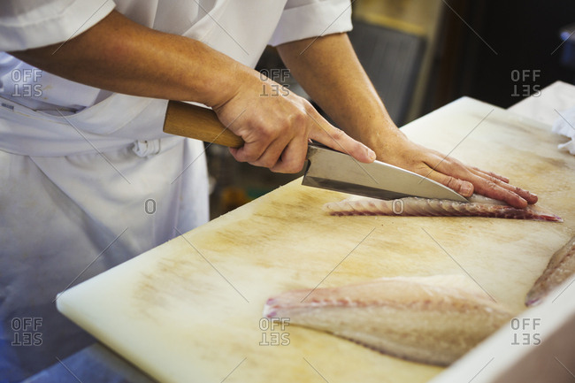 High angle close up of chef working at a counter at a Japanese sushi restaurant, slicing fillet of fish
