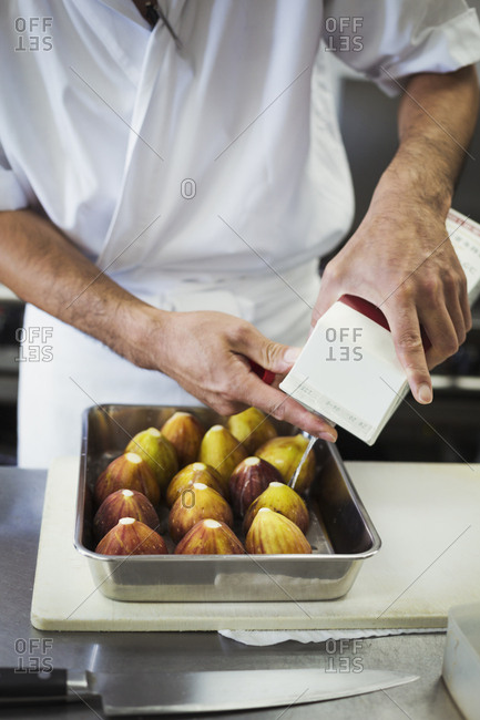 High angle close up of chef working in the kitchen of a Japanese sushi restaurant, preparing figs in a metal tray