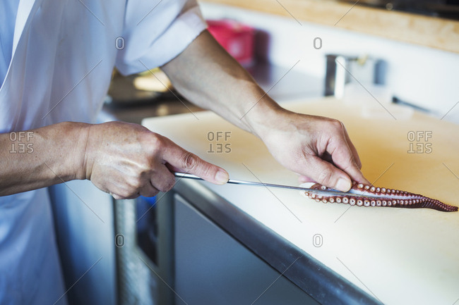 Close up of chef working at a counter at a Japanese sushi restaurant, slicing octopus tentacle